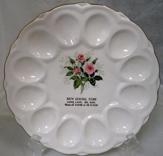 This is a vintage (1940s to 1950s) advertising DEVILED EGG PLATE. It is 9\  in diameter; holds 12 eggs; and has a transfer on the front of a & Vintage Ad\u0027g Egg Plate~RATH STORE Long Lake SD